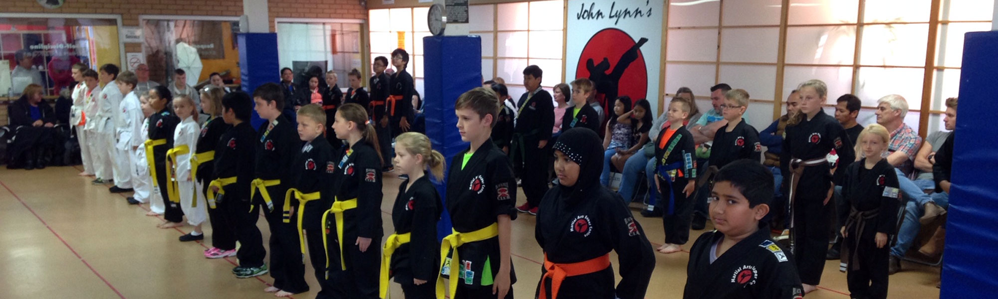 Students standing in John Lynn's Black Belt Academy karate class using merit badges system